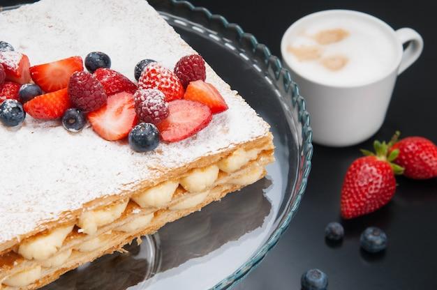 Primer plano de la apetitosa torta de napoleón con bayas y polvo dulce