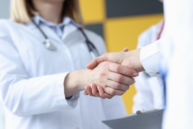 Primer plano del apretón de manos del médico y el paciente en la clínica. concepto de consejo de médicos