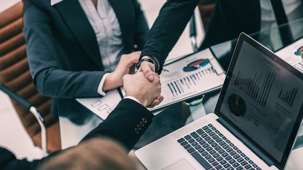 Primer plano del apretón de manos de socios comerciales en el lugar de trabajo en la oficina