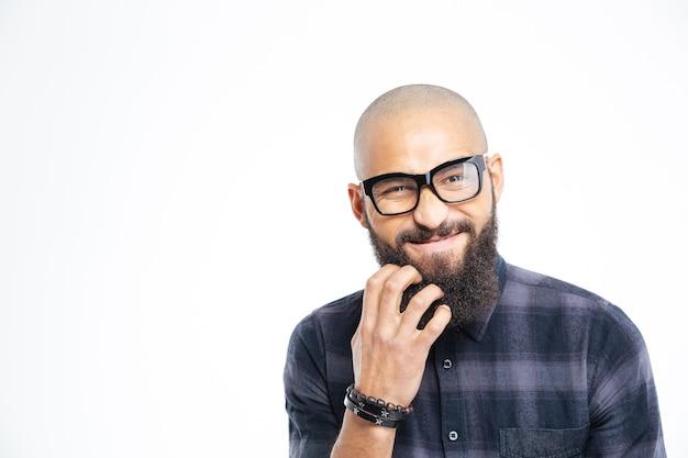 Primer plano de un apuesto joven afroamericano calvo en gafas rascándose la barba