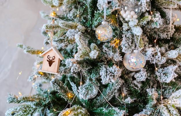 Primer plano de árbol de navidad cubierto de nieve decorado. casa de juguete de madera y guirnalda iluminada con linternas.