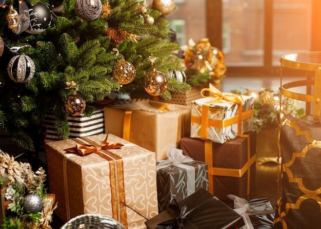 Primer plano de un árbol de navidad decorado con bolas de oro. debajo del árbol de navidad, una gran cantidad de regalos de navidad. concepto de vacaciones de navidad