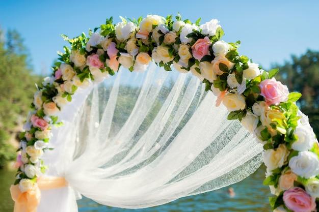 Primer plano de un arco de boda decorado con flores tiernas y tela blanca afuera bajo el cielo azul.