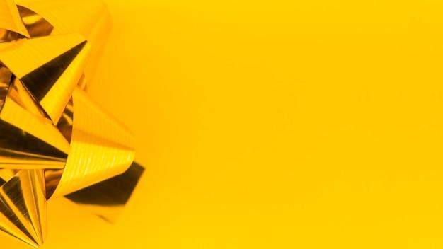 Primer plano del arco de la cinta de oro sobre fondo amarillo
