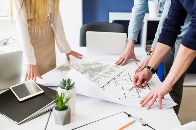 Primer plano de arquitectos dibujo plan sobre plano sobre la mesa en la oficina