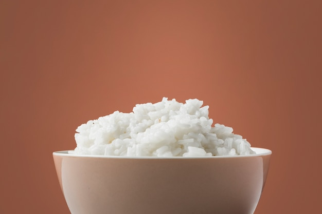 Primer plano de arroz blanco al vapor en un tazón sobre fondo marrón