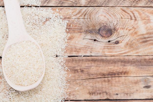 Primer plano de arroz blanco crudo en una cuchara sobre un tablón con textura