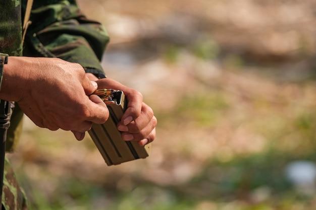 Primer plano de artillero recarga su cargador de pistola, arma de arma, bala del bloque de bala con desenfoque negro