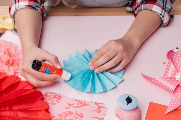 Primer plano de la artista femenina que pega la fan de papel azul de origami