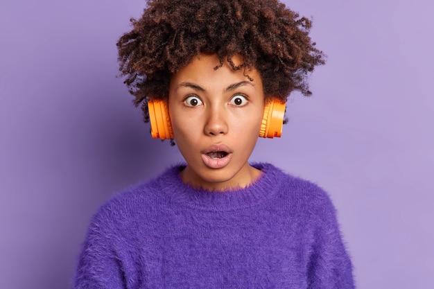 Primer plano de asombrada mujer afroamericana mira fijamente a la cámara con los ojos muy abiertos y la boca tiene el pelo rizado lleva poses de auriculares estéreo