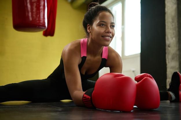 Primer plano de la atleta africana, boxeadora en guantes rojos de boxeo realizando un cordel en el piso de un gimnasio deportivo con un saco de boxeo de boxeo. concepto de estiramiento, deporte y bienestar de arte de combate marcial