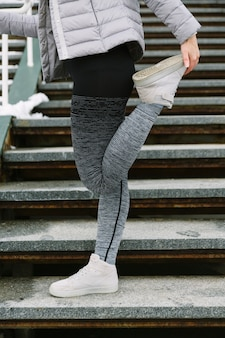 Primer plano de la atleta femenina estirando su pierna en la escalera