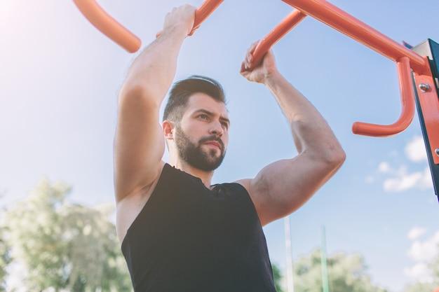 Primer plano de atleta fuerte haciendo pull-up en la barra horizontal. hombre fitness con cielo azul en la pared y espacio abierto a su alrededor. hombre joven con ropa deportiva en la ciudad.