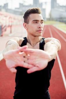 Primer plano de un atleta masculino calentando antes de correr en la pista de atletismo