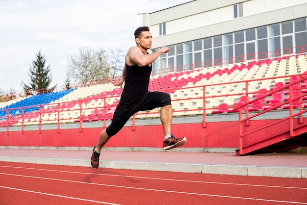 Primer plano de un atleta masculino corriendo en la pista de carreras en el estadio