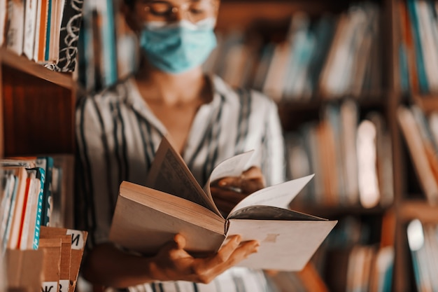 Primer plano de una atractiva chica universitaria de pie en la biblioteca con mascarilla y leyendo un libro. estudiar durante el concepto de virus corona.
