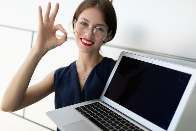 Primer plano de una atractiva joven empresaria con labios rojos con una computadora portátil con una maqueta en sus manos contra el fondo de una pared gris de un edificio de oficinas