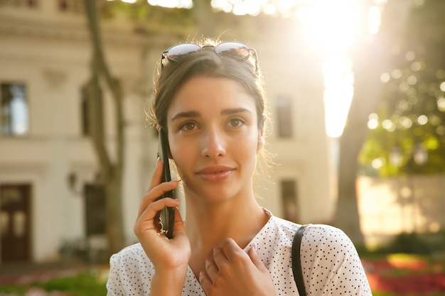 Primer plano de una atractiva joven de pelo oscuro con gafas de sol en la cabeza mirando frente a ella mientras habla por teléfono, caminando sobre la ciudad en un día soleado y cálido