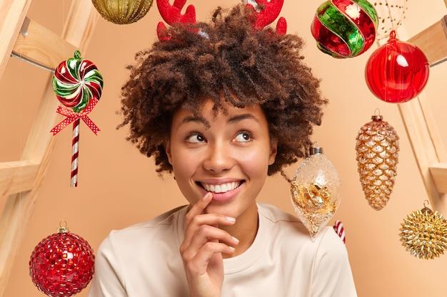Primer plano de una atractiva joven positiva tiene una amplia sonrisa dientes blancos cabello rizado y tupido vestido con ropa casual sueña con un milagro en el año nuevo rodeado de juguetes navideños por encima