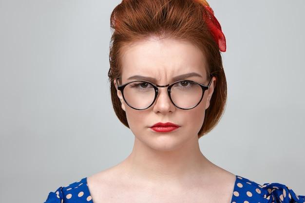 Primer plano de una atractiva joven profesora caucásica con vestido punteado, lápiz labial rojo y elegantes anteojos frunciendo el ceño, mirando a la cámara con expresión estricta, molesta con los alumnos ruidosos