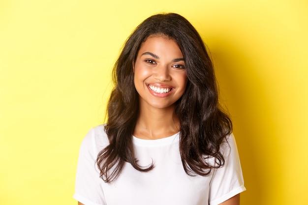 Primer plano de una atractiva mujer afroamericana, sonriendo y mirando feliz, de pie sobre fondo amarillo
