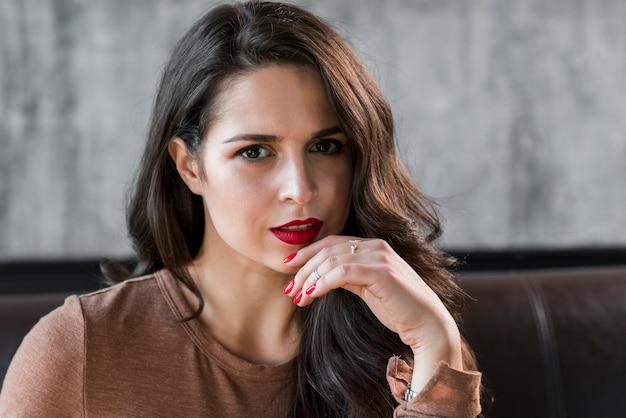 Primer plano de una atractiva mujer joven con labios rojos y esmalte de uñas en los dedos