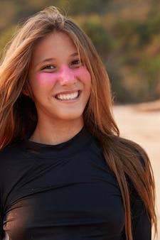 Primer plano de atractiva surfgirl vestida con traje de neopreno negro, tiene una máscara rosa en su cara bonita, tiene el pelo largo