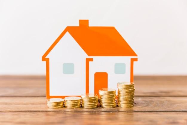 Primer plano de aumento de monedas apiladas y modelo de la casa en el escritorio de madera
