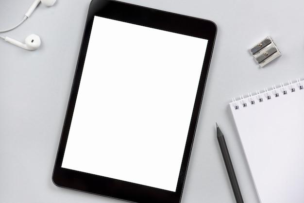 Primer plano de auricular; tableta digital en blanco; sacapuntas; bloc de notas de lápiz y espiral sobre fondo gris