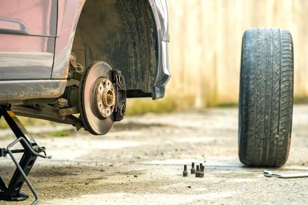 Primer plano de un automóvil levantado en el gato en proceso de reemplazo de neumáticos de ruedas nuevas. desglose de un vehículo en una calle.