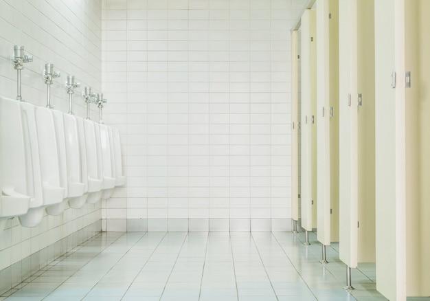 Primer plano de azulejos de la pared en el inodoro del hombre con vista de inodoro por urinarios y habitación pequeña