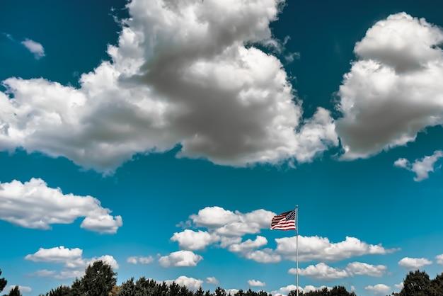 Primer plano de la bandera estadounidense ondeando en el aire bajo un cielo nublado
