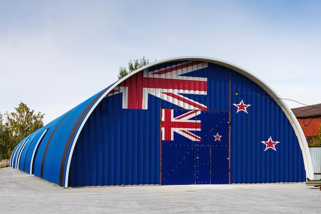 Primer plano de la bandera nacional de nueva zelanda pintada en la pared de metal de un gran almacén del territorio cerrado contra el cielo azul.