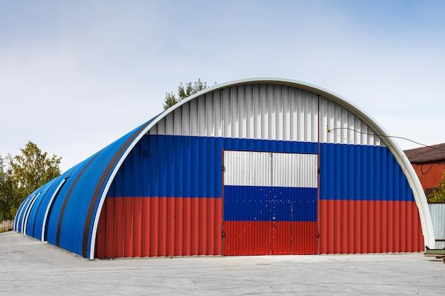 Primer plano de la bandera nacional de russia pintado en la pared de metal de un gran almacén del territorio cerrado contra el cielo azul. el concepto de almacenamiento de mercancías, entrada a un área cerrada, logística.