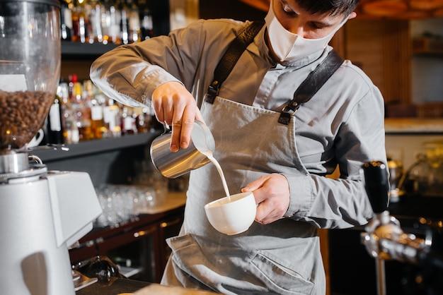 Primer plano de un barista enmascarado preparando un delicioso café en el bar de una cafetería