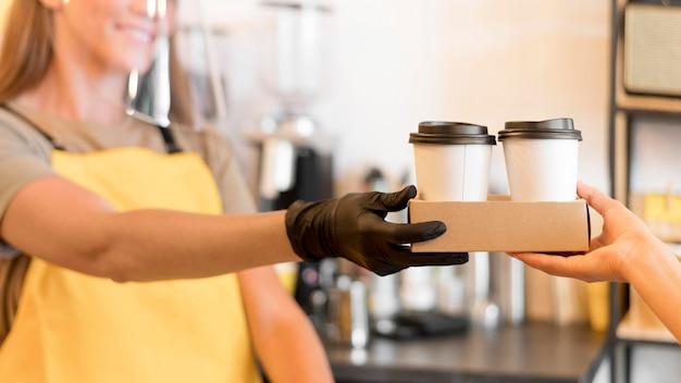 Primer plano barista con guantes trabajando