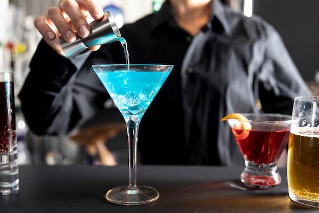 Primer plano barista vertiendo líquido alcohólico en vidrio