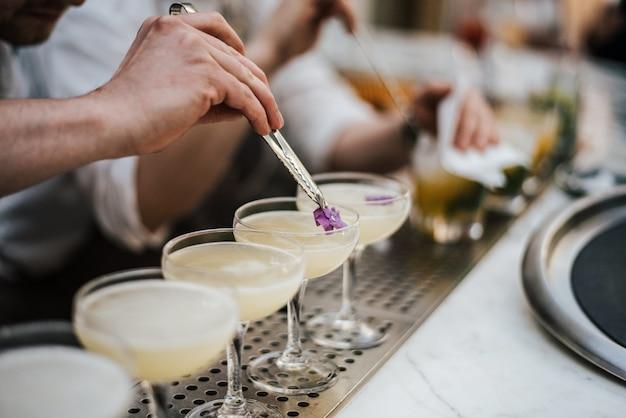Primer plano de un barman haciendo margaritas con cinco vasos en línea