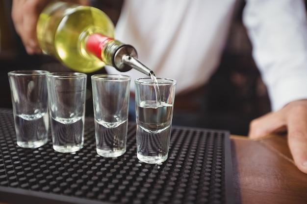Primer plano de barman vertiendo tequila en vasos de chupito