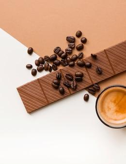 Primer plano de barra de chocolate y granos de café tostados con vaso de café sobre doble fondo