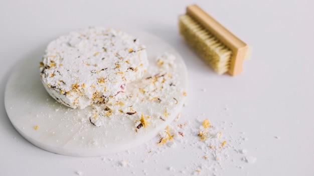 Primer plano de la barra de jabón roto y pincel sobre superficie blanca