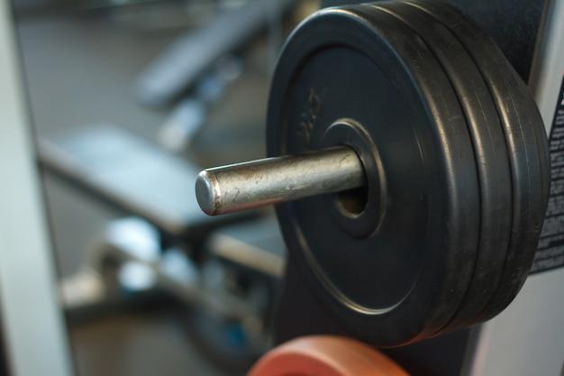 Primer plano de una barra con pesas en un gimnasio, fondo o concepto de levantamiento de pesas y deportes