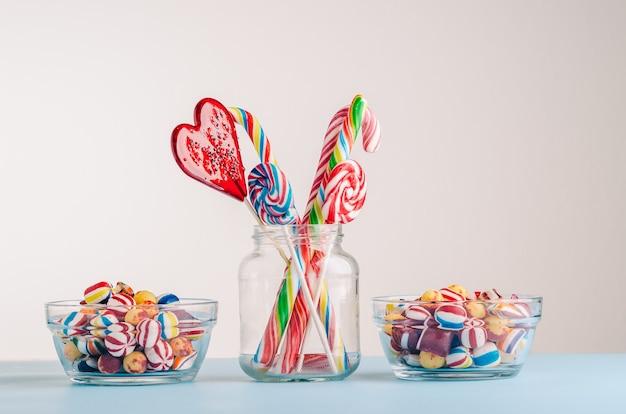 Primer plano de bastones de caramelo y otros dulces en frascos de vidrio, perfecto para un fondo de pantalla genial