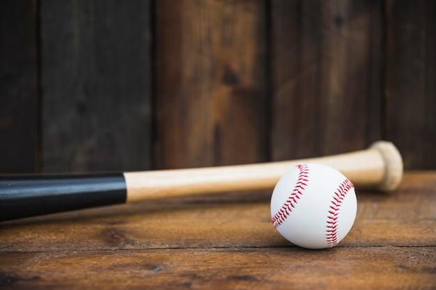 Primer plano de bate de béisbol y bola blanca en mesa de madera