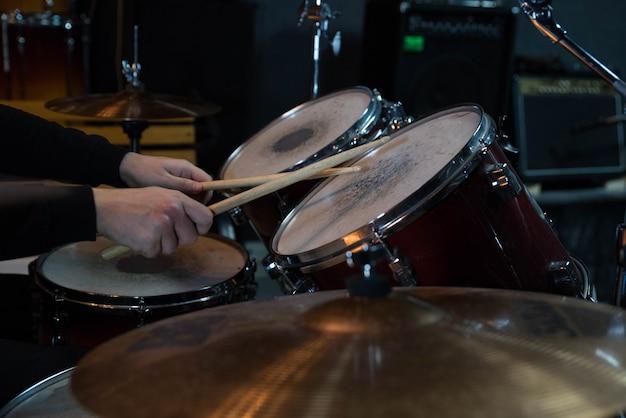 Primer plano de batería profesional. hombre baterista con baquetas tocando tambores y platillos, en el concierto de rock de música en vivo o en el estudio de grabación