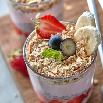 Primer plano de batido de yogur orgánico con fresas, plátano, arándano, copos de avena y semillas de chía