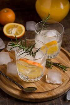 Primer plano de bebidas aromáticas con romero y naranja