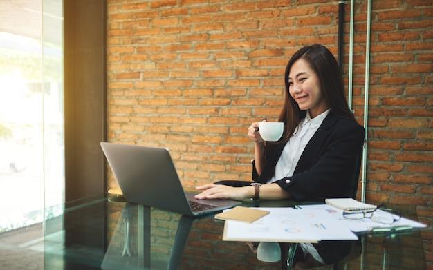 Primer plano de una bella empresaria asiática bebiendo café mientras usa y trabaja en la computadora portátil en la oficina