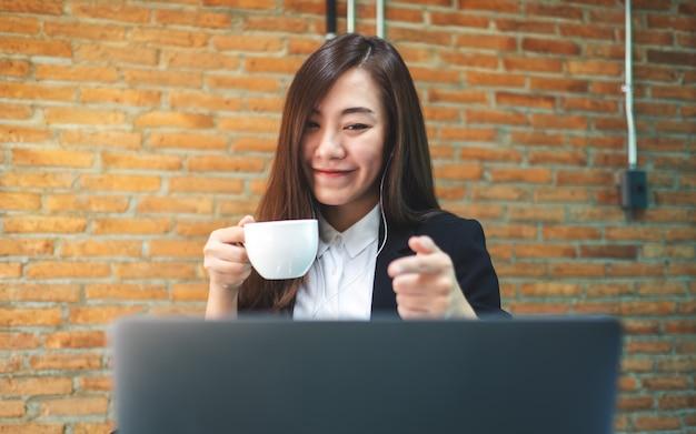 Primer plano de una bella empresaria usando auriculares para video conferencia en la computadora portátil mientras bebe café y trabaja en línea