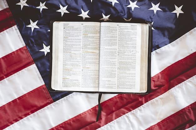 Primer plano de la biblia abierta en páginas puestas en la bandera estadounidense - perfecto para el concepto de oración